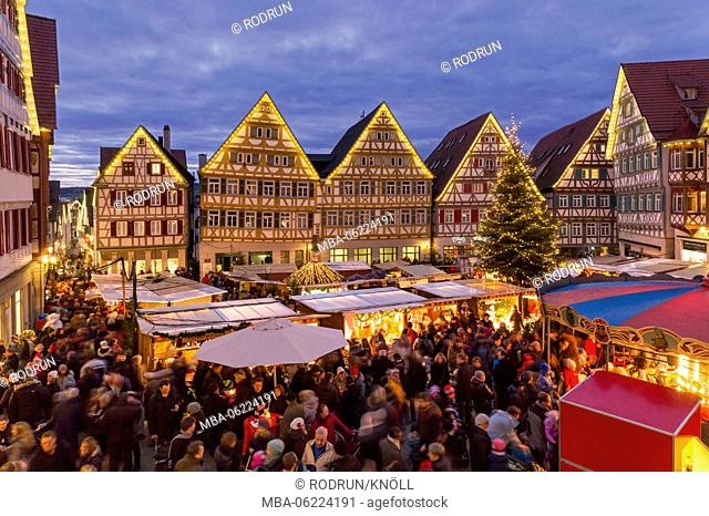 Germany, Baden-Württemberg, Herrenberg, Christmas market, view to the market square with market stalls and visitors to the half-timbered houses of the...