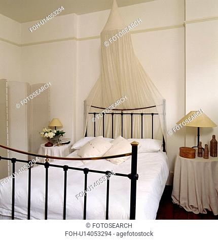 White moxsquito bet above black iron bed with white linen in white bedroom