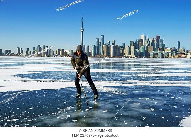 Hockey player and city skyline from Ward's Island; Toronto, Ontario, Canada