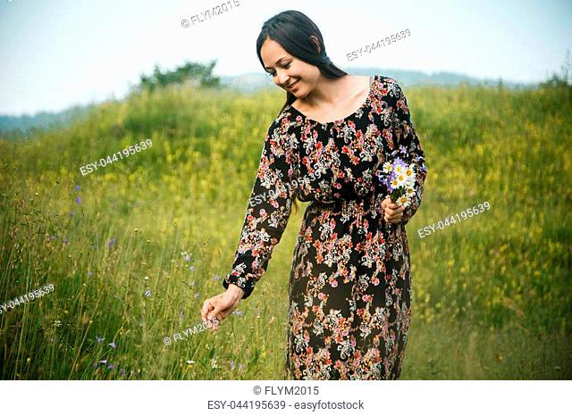 beautiful girl in long dress picking flowers on the meadow