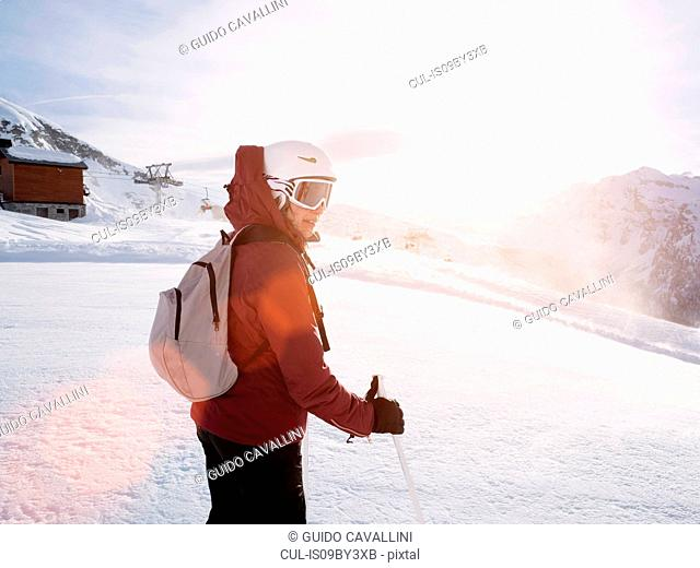 Young woman skier wearing helmet and ski goggles in snow covered landscape, Alpe Ciamporino, Piemonte, Italy