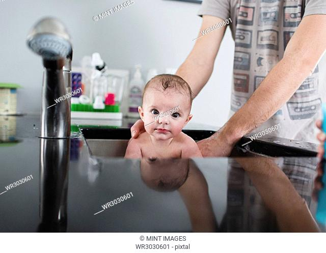 A mother, woman bathing a baby girl in a sink