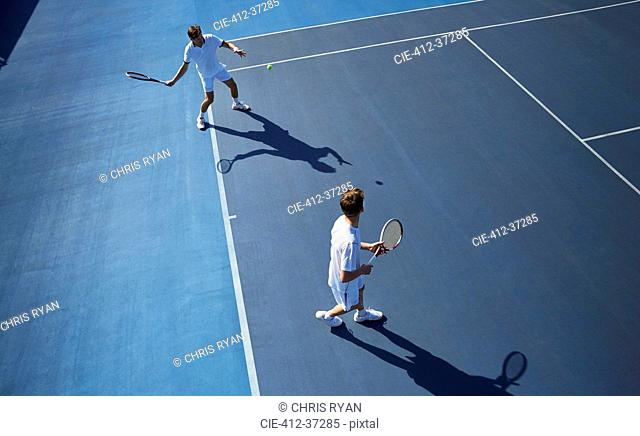 Young male doubles tennis players playing tennis on sunny blue tennis court
