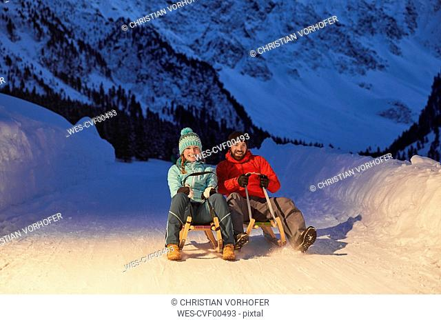 Happy couple sledding in snow-covered landscape at night