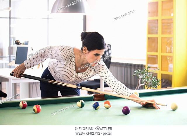 Determined businesswoman playing pool billard in modern office