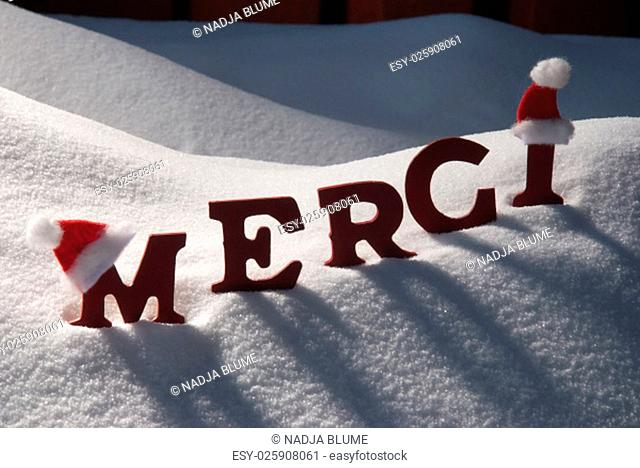 Red Letters With Santa Hat On White Snow As Christmas Card. French Text Or Word Merci Mean Thank You. Snowy Scenery And Atmosphere