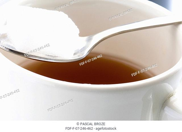 Close-up of a tea cup with sugar cubes on a spoon