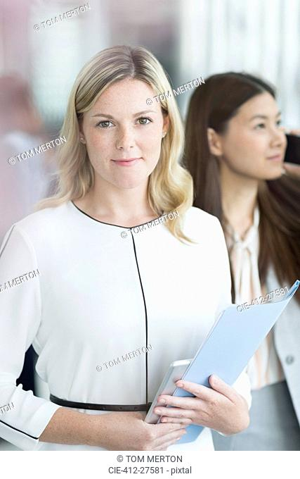 Portrait confident businesswoman with folder and digital tablet