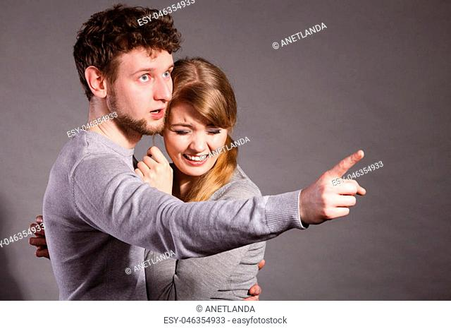 Fear and scare. Two young terrified scared people. Stressed woman and man showing to copy space. Couple afraid of bad things war