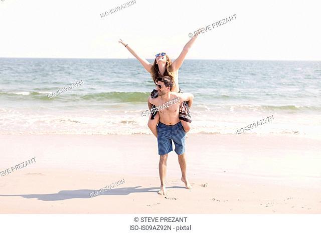 Man on beach giving woman piggyback, Coney island, Brooklyn, New York, USA