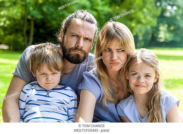 Portrait of playful family pulling faces outdoors