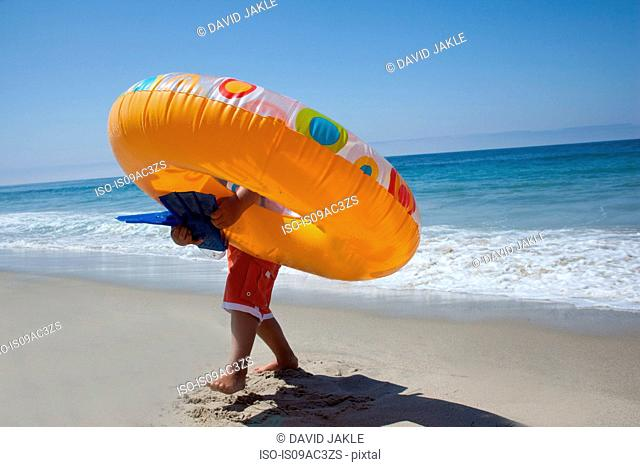 Young boy carrying rubber ring on beach