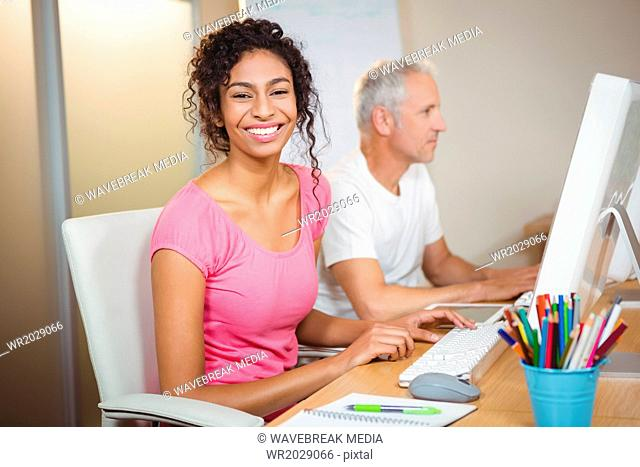 Portrait of happy businesswoman working on computer