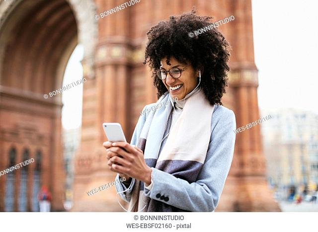 Spain, Barcelona, happy woman with cell phone and earphones at a gate