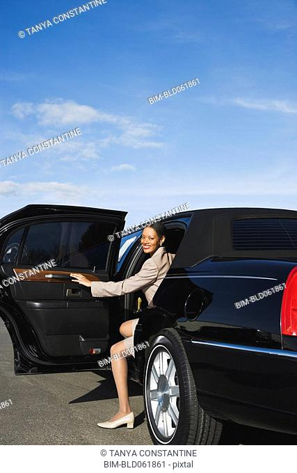 African businesswoman getting out of limousine