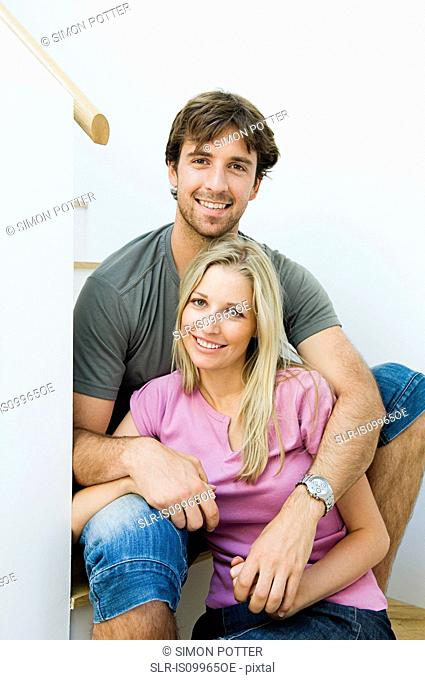 Young couple smiling on staircase