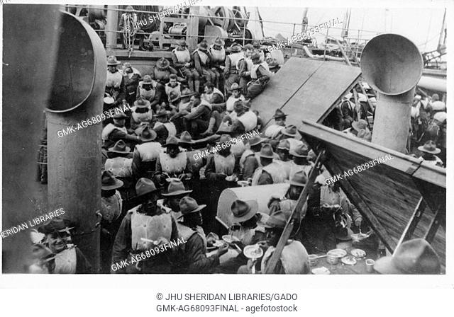 A large group of African-American sailors wearing hats and flotation vests, some of whom are eating, is gathered on the deck of an American Navy vessel, 1915