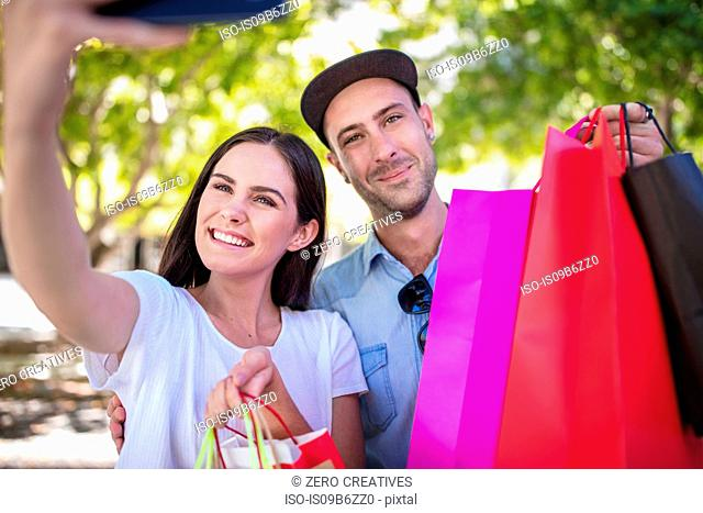 Young couple outdoors, holding colourful shopping bags, taking selfie, using smartphone