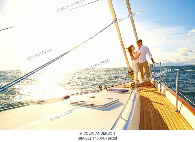 Caucasian couple hugging on yacht deck