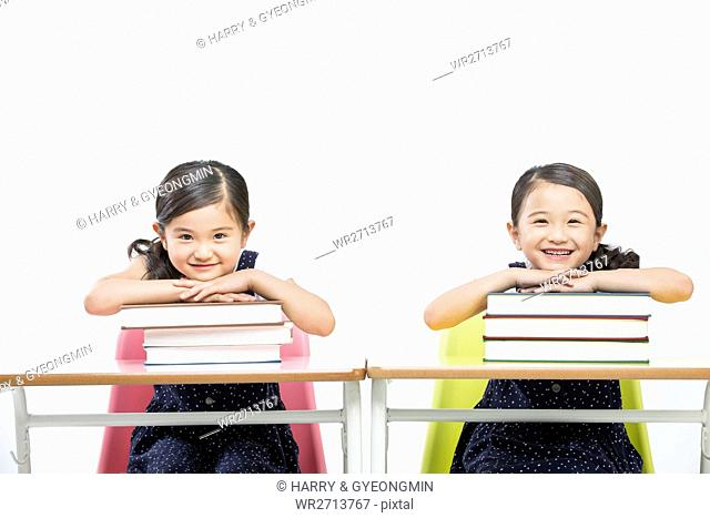 Smiling twin girls with stacked books