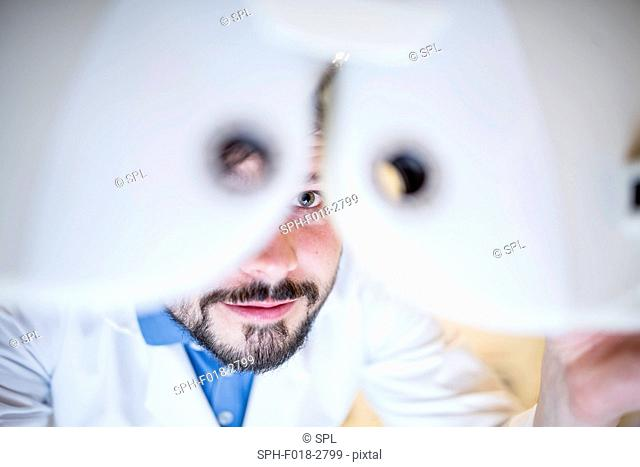 Optometrist performing eye test in optometrist's shop, close-up