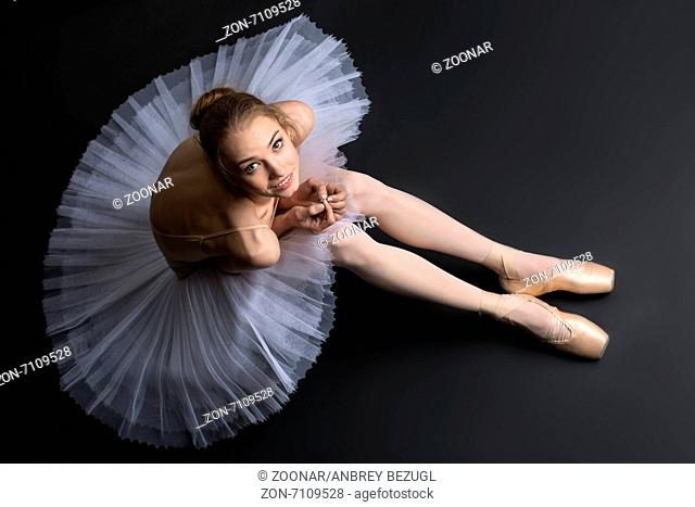 Young, graceful ballerina sitting on the floor on a black background in the studio looking at the top of the camera with a smile and tender emotion