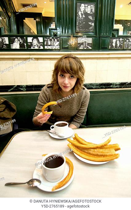 young woman enjoying churros dipped in hot chocolate dipping sauce, San Gines chocolateria in Madrid, Spain, Europe