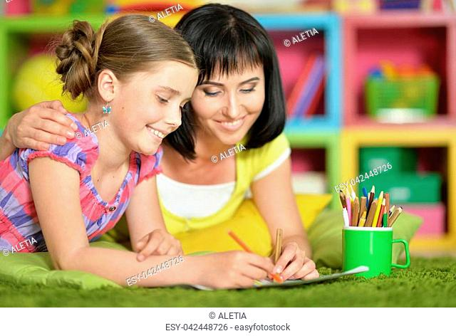 Cute girl lying on floor and doing homework with her mother