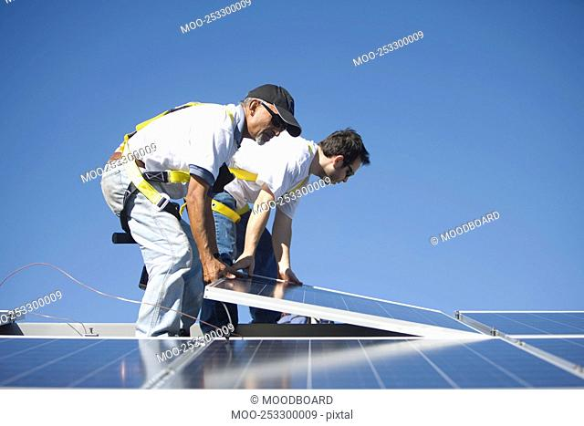 Two men lifting a solar panel