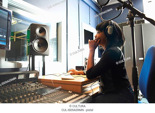 Side view of young woman wearing headphones, sitting at mixing desk in recording studio looking at monitor