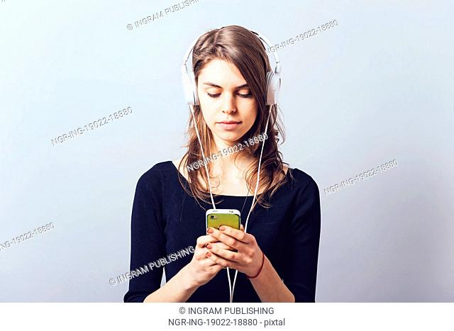 Woman with headphones and listening to music on a grey background
