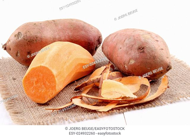 peeled sweet potato and potato peel on jute