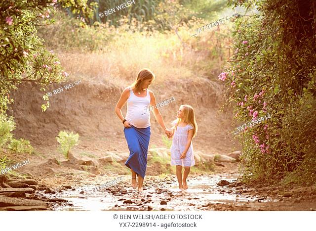 Mother and daughter walking together outdoors