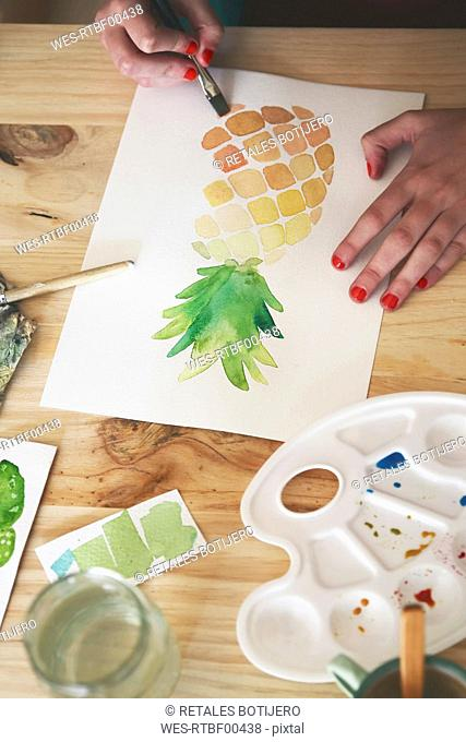 Woman's hand painting aquarelle of a pineapple at desk in her studio