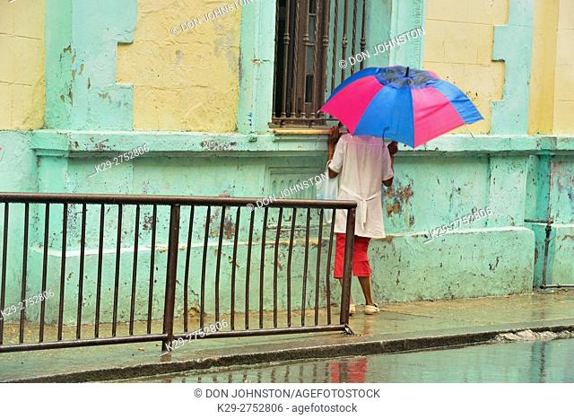 Street photography in central Havana- Reflections of a school building in wet pavement on a rainy day with passersby, La Habana (Havana), Habana, Cuba
