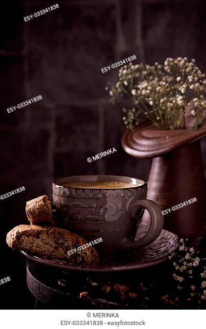Coffee cup with cookies and coffee beans on dark rustic background with space for text. Toned