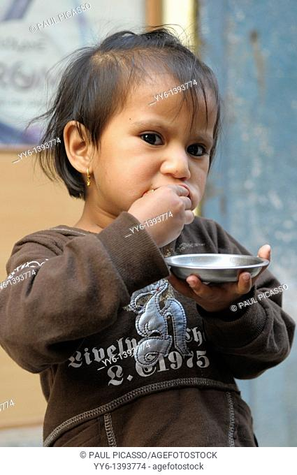 little nepalis girl eating , the nepalis , life in kathmandu , kathmandu street life , nepal