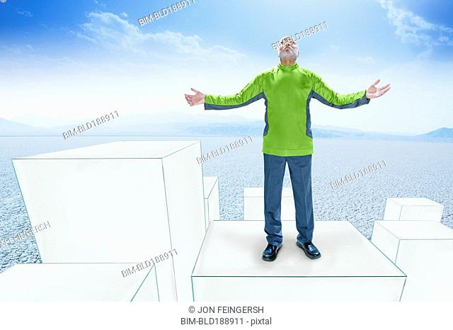 African man standing on drawings of boxes with arms outstretched