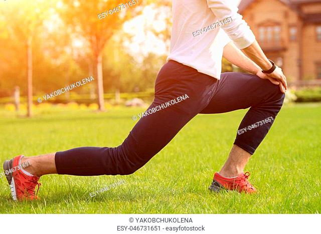 Skillful male athlete is warming up before running. He is standing and kneeling on grass