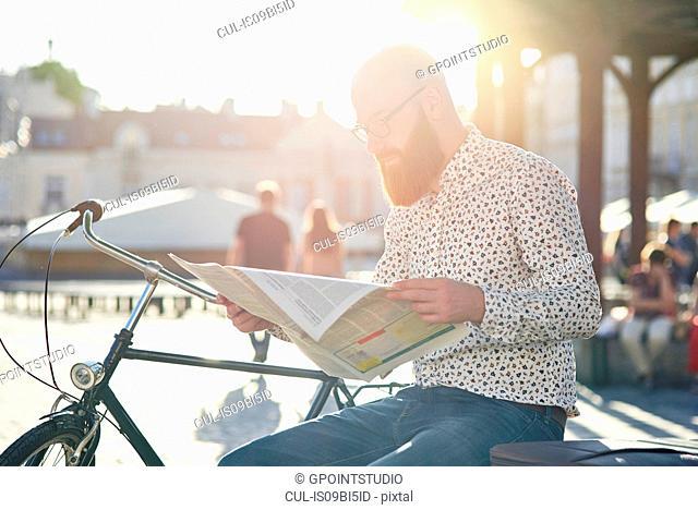 Bearded man reading newspaper in street