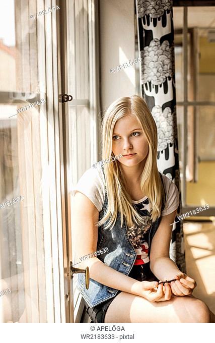 Thoughtful girl looking through window in school