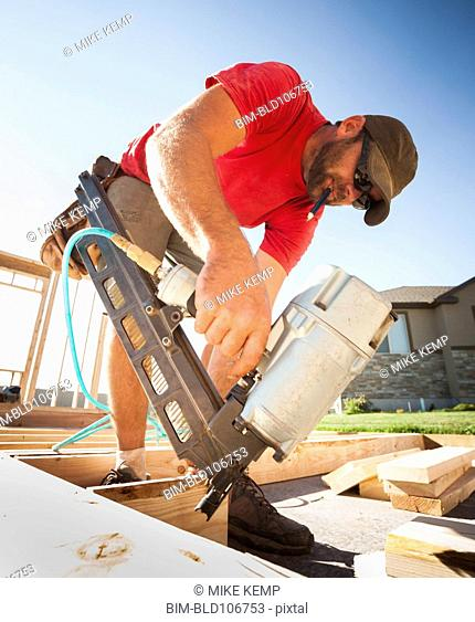 Caucasian man using nail gun on frame