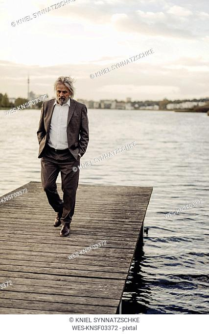 Senior man walking on jetty at a lake