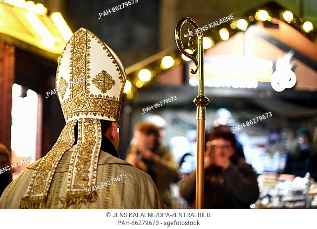 Actor Philipp Ploog dressed as St. Nicholas distributes presents at the Nostalgic Christmas Market outside St. Hedwig's cathedral in Berlin, Germany