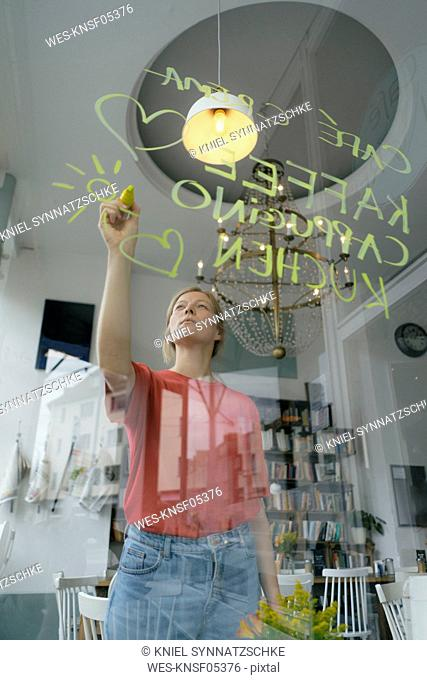 Young woman writing offer on windowpane in a cafe