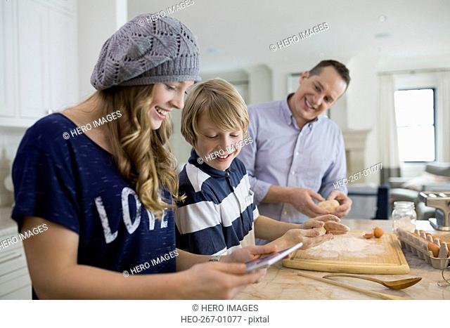 Brother and sister researching baking recipe digital tablet