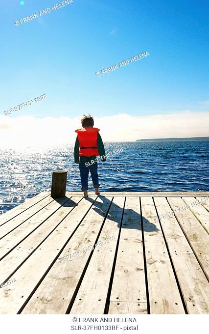 Boy wearing lifejacket on wooden pier