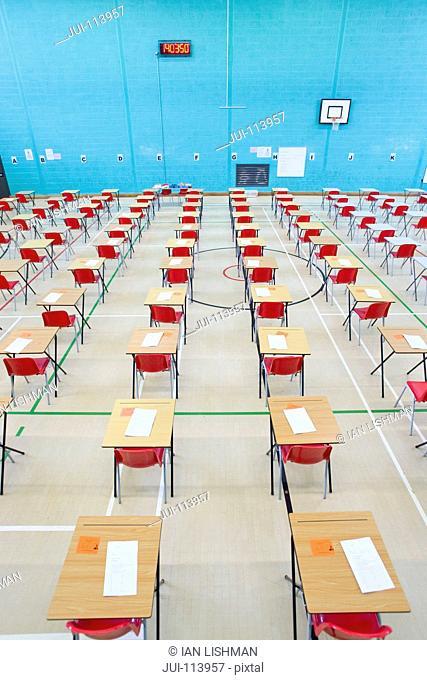 Rows of desks with examinations ready in school gymnasium