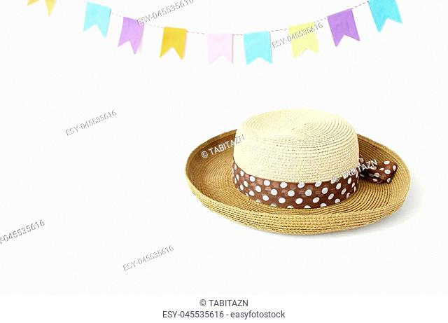 Straw hat on white table with colorful party flags, bunting decoration. Greeting card, invitation for summer birthday or Brazilian june party