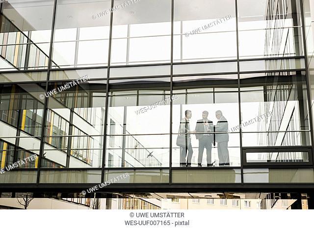Three businessmen behind glass facade